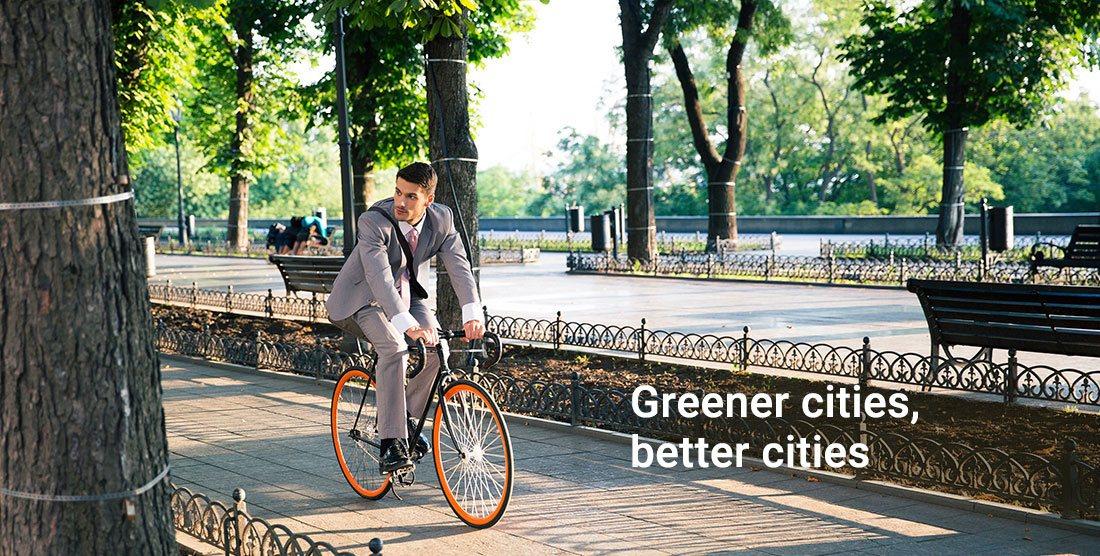 Man riding a bike through a green cityscape